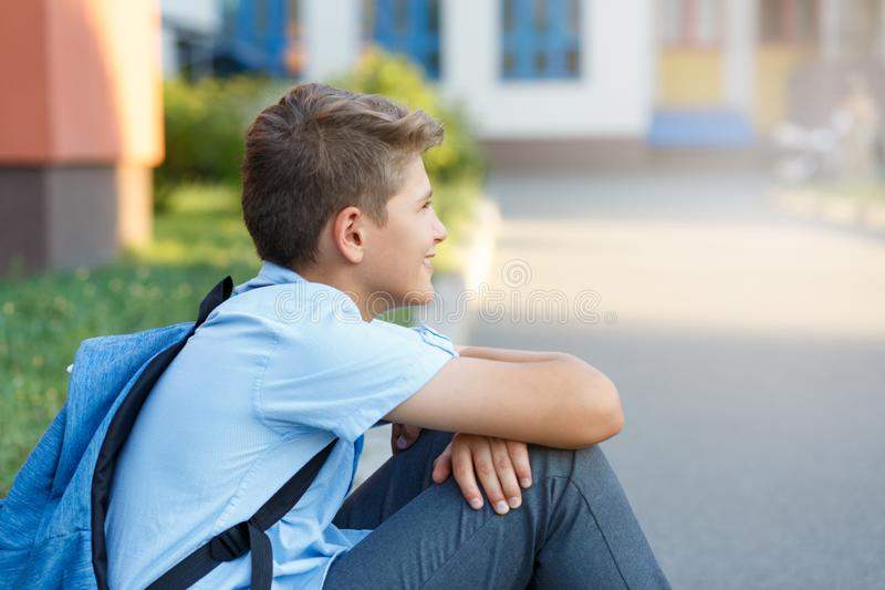Cute, nice, young 11 years old boy in blue shirt stands with workbooks and backpack in front of his school. Education. Back to school concept royalty free stock image