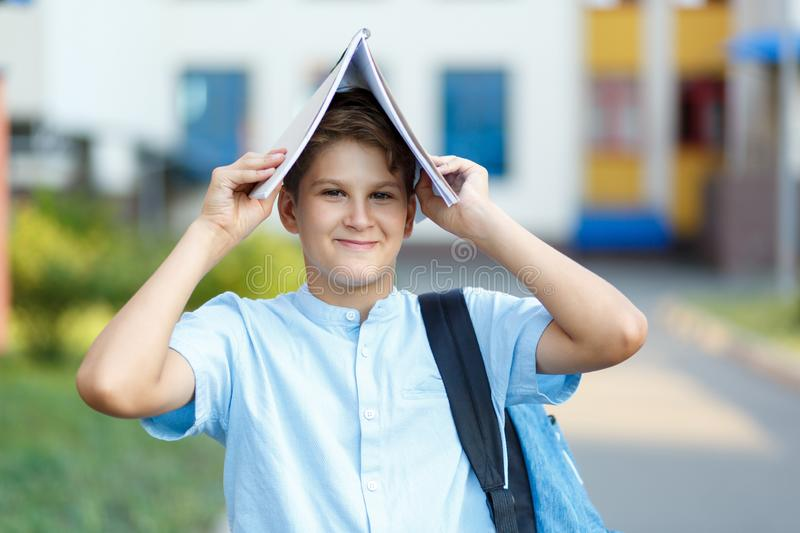 Cute, nice, young 11 years old boy in blue shirt stands with workbooks and backpack in front of his school. Education. Back to school concept royalty free stock photography