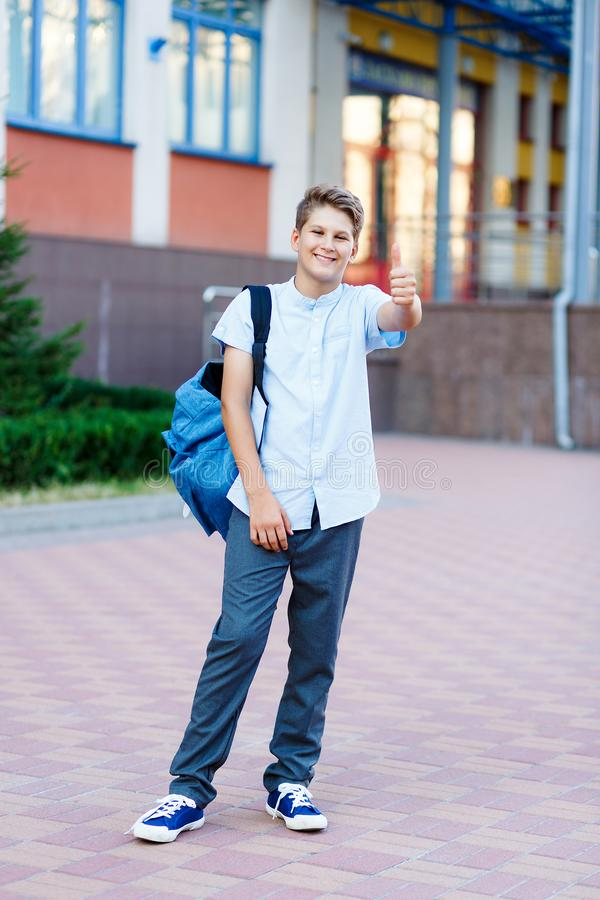 Cute, nice, young 11 years old boy in blue shirt stands with workbooks and backpack in front of his school. Education. Back to school concept royalty free stock photos