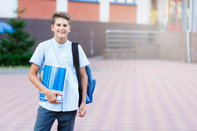 Cute, nice, young 11 years old boy in blue shirt stands with workbooks and backpack in front of his school. Education. Back to school concept royalty free stock images