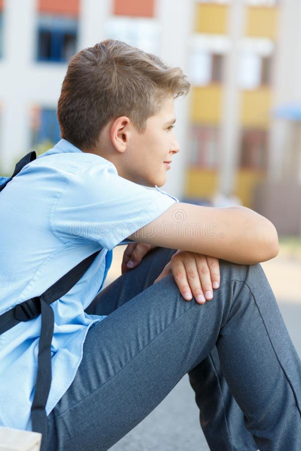 Cute, nice, young 11 years old boy in blue shirt stands with workbooks and backpack in front of his school. Education. Back to school concept stock image