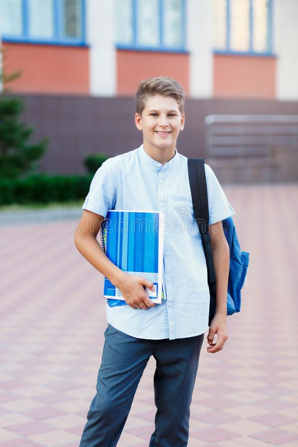 Cute, nice, young 11 years old boy in blue shirt stands with workbooks and backpack in front of his school. Education. Back to school concept stock photos