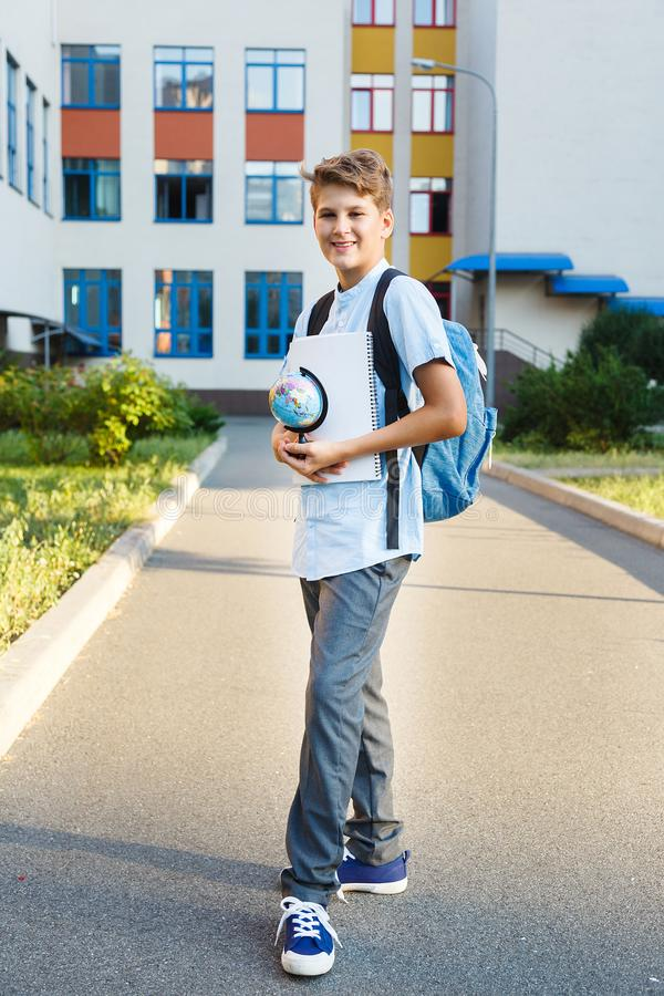 Cute, nice, young 11 years old boy in blue shirt stands with workbooks and backpack in front of his school. Education. Back to school concept stock photo