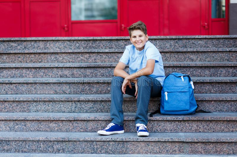 Cute, nice, young 11 years old boy in blue shirt stands with workbooks and backpack in front of his school. Education. Back to school concept stock photography