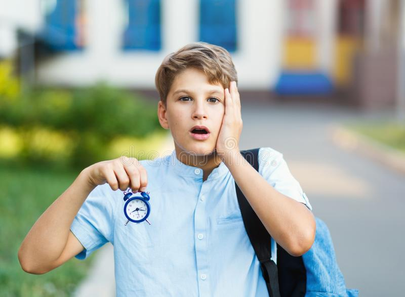 Cute, nice, young 11 years old boy in blue shirt stands with workbooks in front of his school. Education, back to school royalty free stock photography