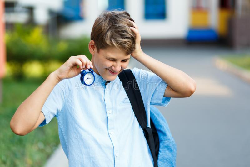 Cute, nice, young 11 years old boy in blue shirt stands with workbooks in front of his school. Education, back to school. Cute, nice, young 11 years old boy in stock photography