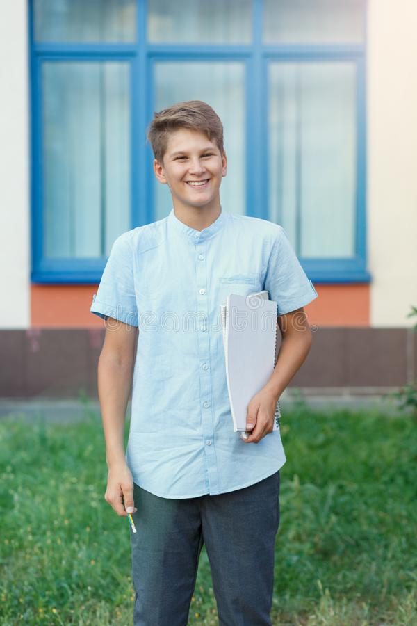 Cute, nice, young 11 years old boy in blue shirt stands with workbooks in front of his school. Education, back to school. Concept royalty free stock images