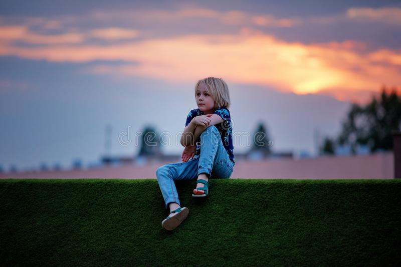 Cute, nine year old boy in thoughts over the sunset skies royalty free stock photos