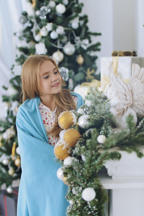Cute nine year old girl. Pretty nine year old girl in pajama and covered with a blanket posing near the fireplace decorated for Christmas. Time for miracles royalty free stock photo