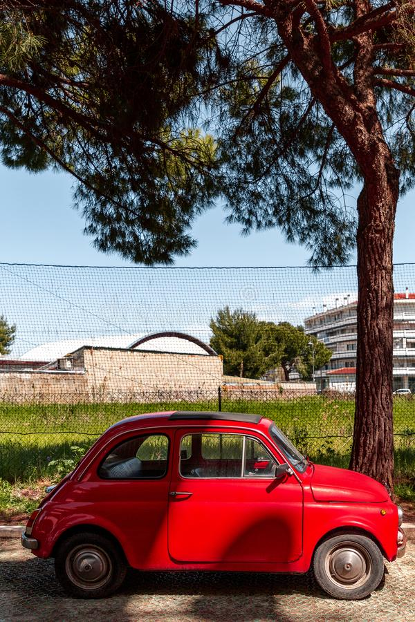 Cute old fashioned red car. Parked on a green italian avenue in Pescara city stock images