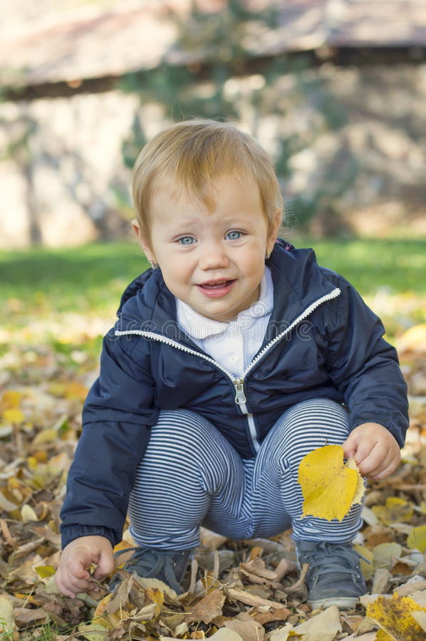 Cute one year old baby girl sitting on grass in a park stock photo