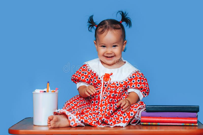 Cute one year old mixed race Asian Caucasian german girl wearing red dress smiles sweetly looking at the camera on blue background.  stock photos