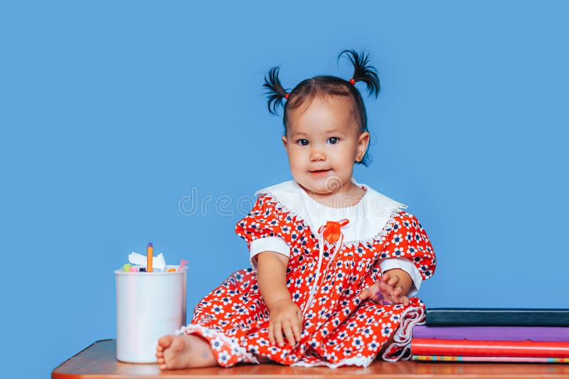 Cute one year old mixed race Asian Caucasian german girl wearing red dress smiles sweetly looking at the camera on blue background.  stock image