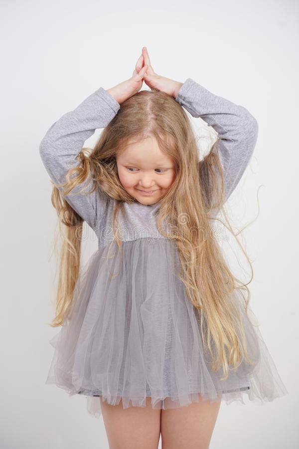 Cute orphan girl stands and holds her hands over her head in the form of a house, dreaming of an apartment, on a white background. In the Studio stock photo