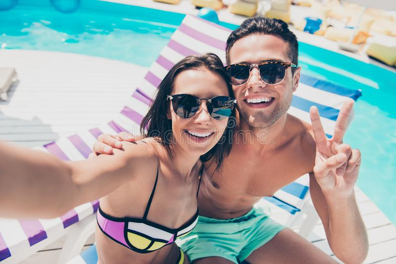 Cute pair spending honeymoon enjoying sunny day taking selfies showing v-sign symbol. Cute pair spending, honeymoon enjoying sunny day taking selfies showing v stock photography
