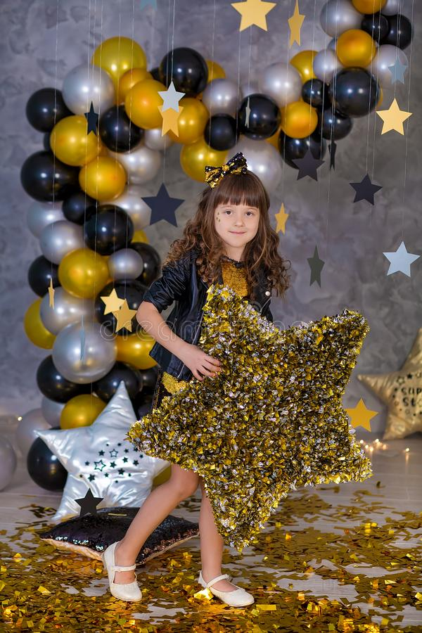 Cute party girl in golden dress posing in club studio with golden stars and air baloons. Pillow stars SUPER STAR designed by royalty free stock photos