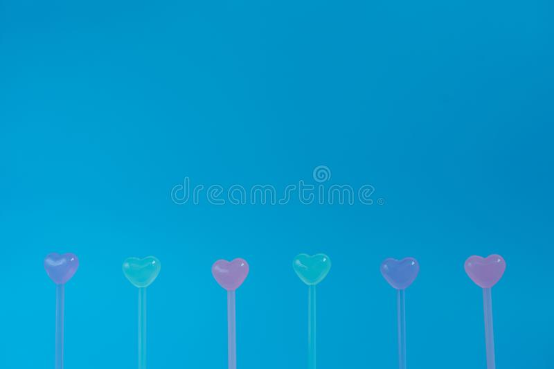 Cute pastel colorful of little heart shape line up, frame and border on the bottom of blue background, for advertising mockup or stock image