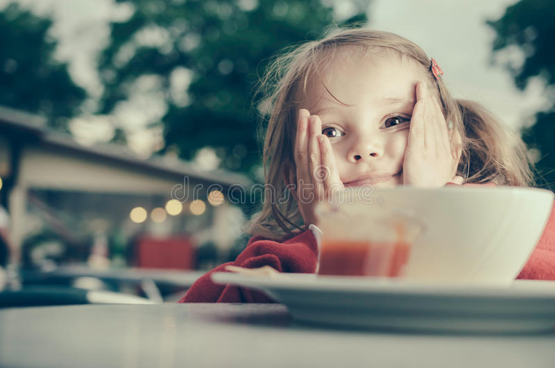 Cute pensive little girl with elbows on the table stock photos