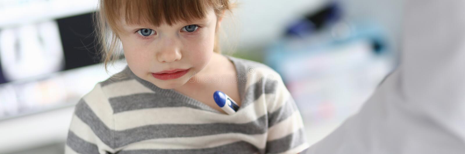 Cute pensive little girl with thermometer under her armpit stock photo