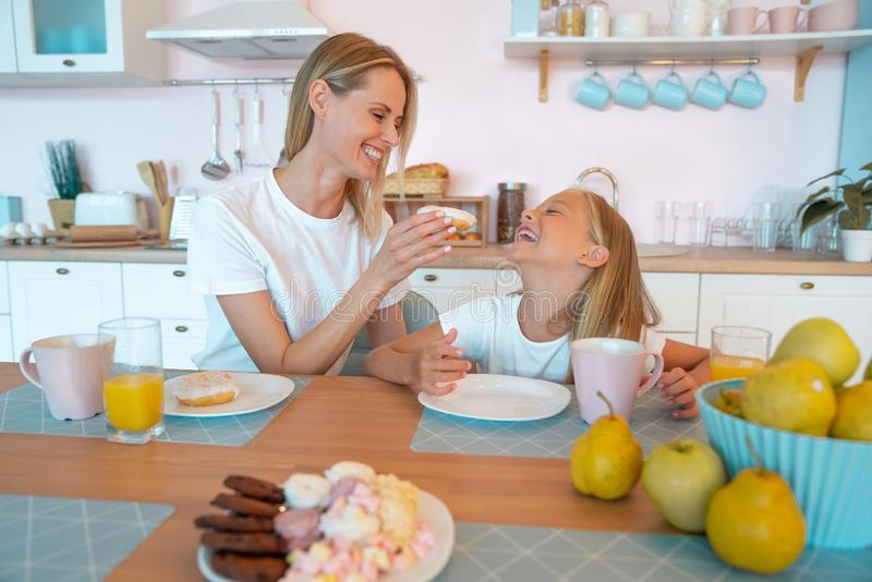 Cute photo of mom and daughter having breakfast with donuts and tea. cuddling and looking at the camera royalty free stock images