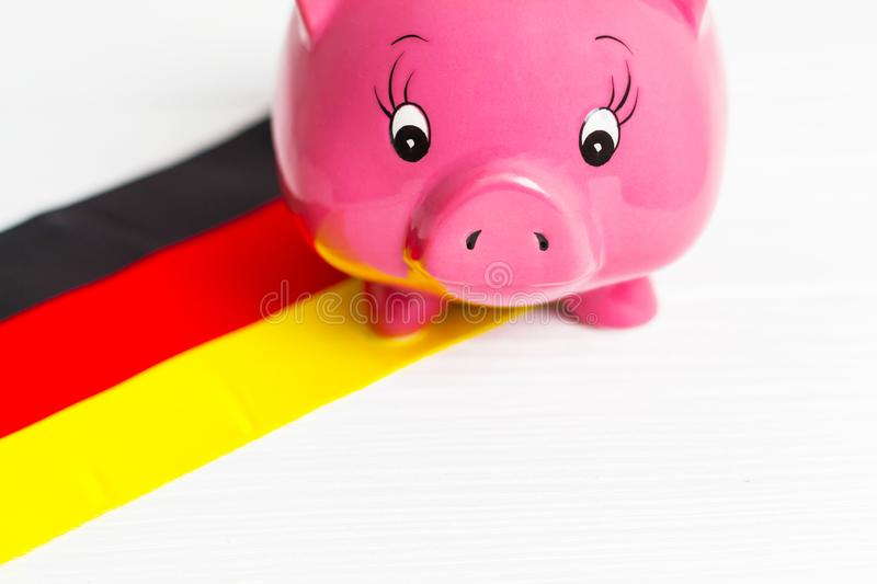 Cute pig money box and Germany flag - save money in Germany concept.  royalty free stock images