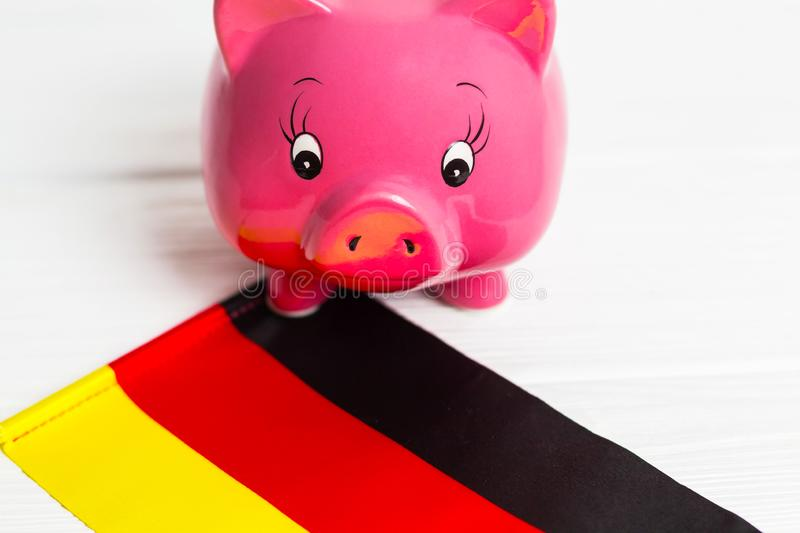 Cute pig money box and Germany flag - save money in Germany concept. Closedup. Cute pig money box and Germany flag - save money in Germany concept stock photography