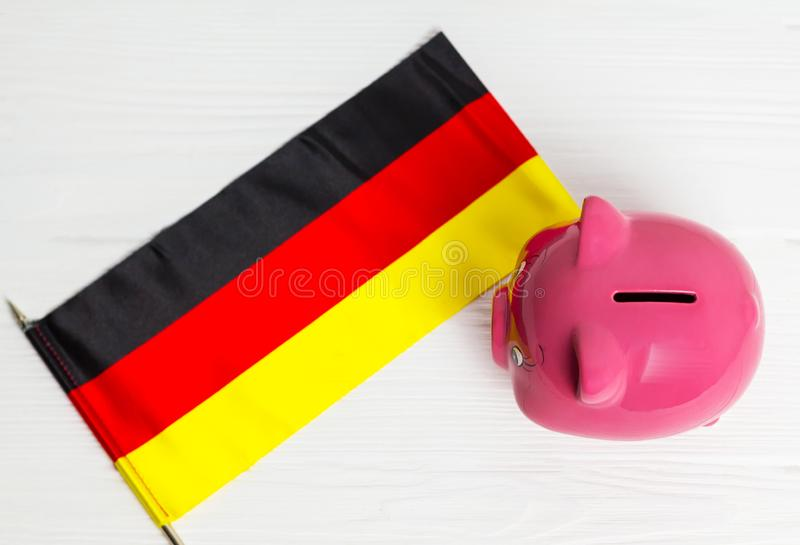Cute pig money box and Germany flag - save money in Germany concept. view from above. Cute pig money box and Germany flag - save money in Germany concept stock image