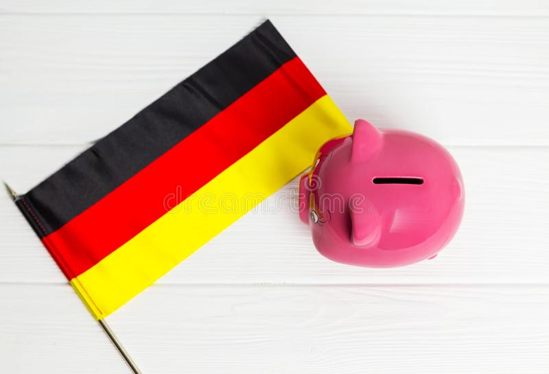 Cute pig money box and Germany flag - save money in Germany concept. view from above. Cute pig money box and Germany flag - save money in Germany concept royalty free stock photography