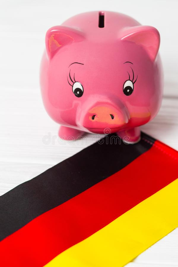 Cute pig money box and Germany flag - save money in Germany concept. Vertical. Cute pig money box and Germany flag - save money in Germany concept royalty free stock photo