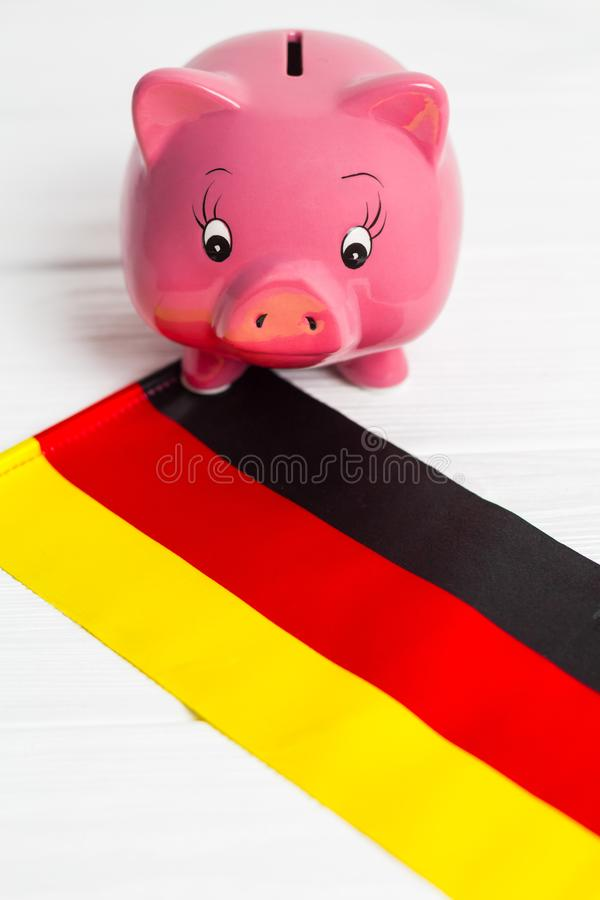 Cute pig money box and Germany flag - save money in Germany concept.  stock photos