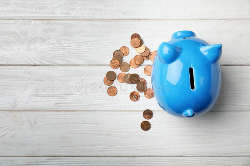 Cute piggy bank and coins on wooden background. Top view with space for text royalty free stock photography