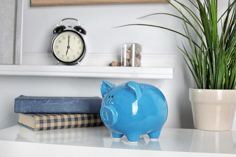 Cute piggy bank on table indoor. S. Stylish interior royalty free stock image