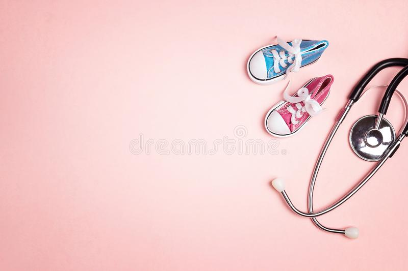 Cute pink baby girl and blue baby boy shoes with stethoscope on pink background. Top view with copy space stock image