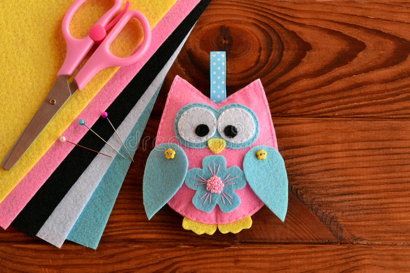 Cute pink and blue owl toy, colored felt sheets, scissors on a wooden table. Fabric owl embellishment royalty free stock photography