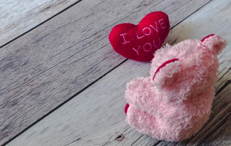 Cute pink Teddy bear looks at red heart ` I Love You `. On white wooden retro style floor. Minimal and simple love photo concept. Copy space for text. Love is royalty free stock photo