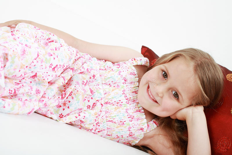 Cute playful little girl relaxing stock photo