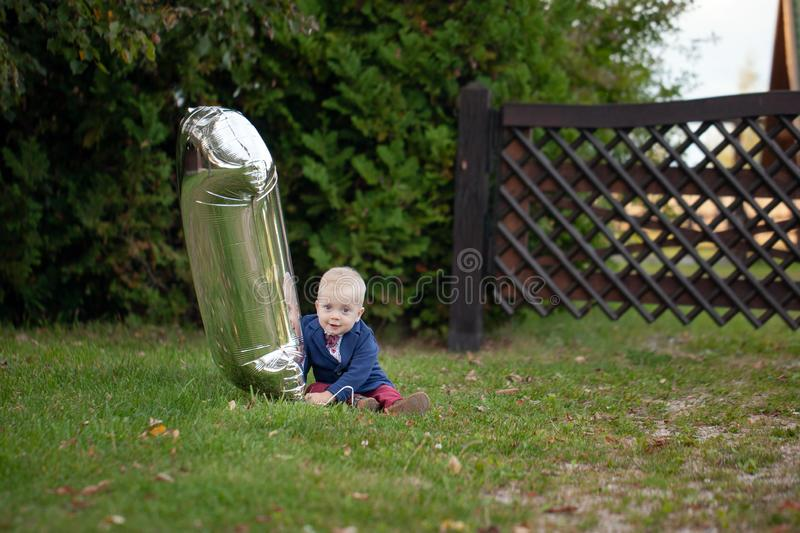 Cute playful smiled blond. 1 years old boy sitting on green grass outdor in summer day stock photos