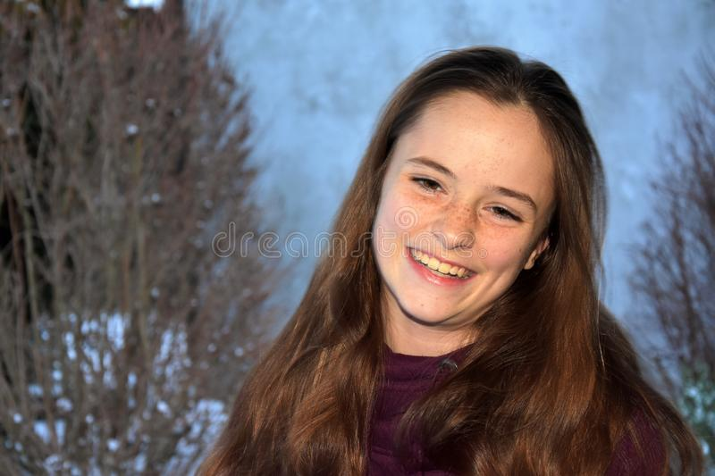 Cute teenage girl smiles with malicious joy royalty free stock photography