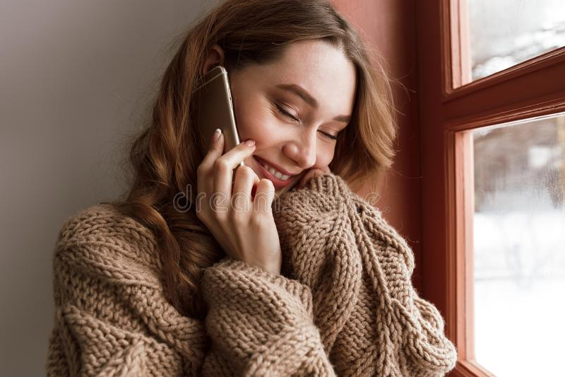 Cute pleased woman 20s with brown hair holding phone, and enjoying mobile conversation near window indoor stock image