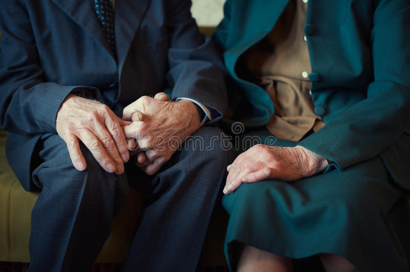 Cute 80 plus year old married couple posing for a portrait in their house. Love forever concept. Close up portrait, couple holding hands royalty free stock image