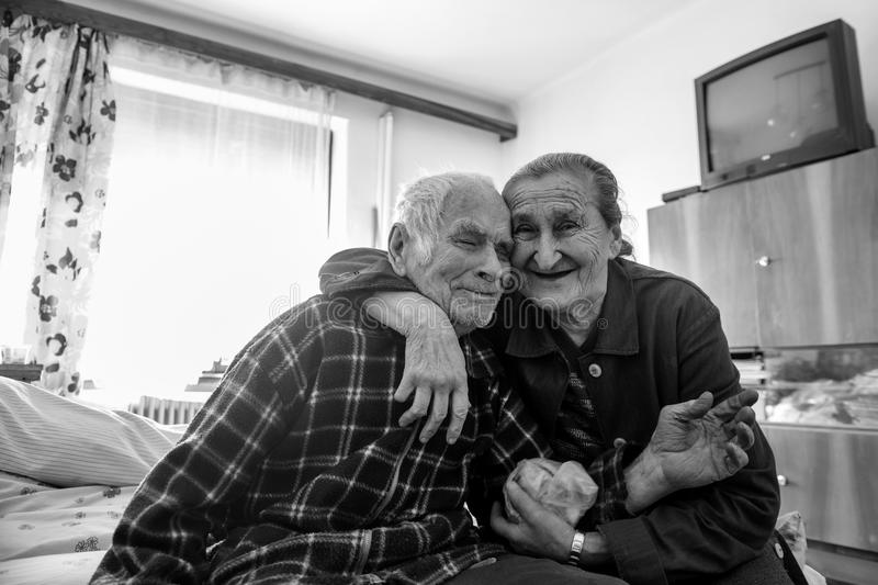 Cute 80 plus year old senior married couple hugging and smiling portrait. Black and white waist up image of happy elderly couple. royalty free stock photography