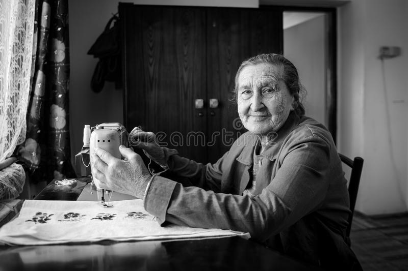 Cute 80 plus year old senior woman using vintage sewing machine. Black and white image of adorable elderly woman sewing clothes. stock photo