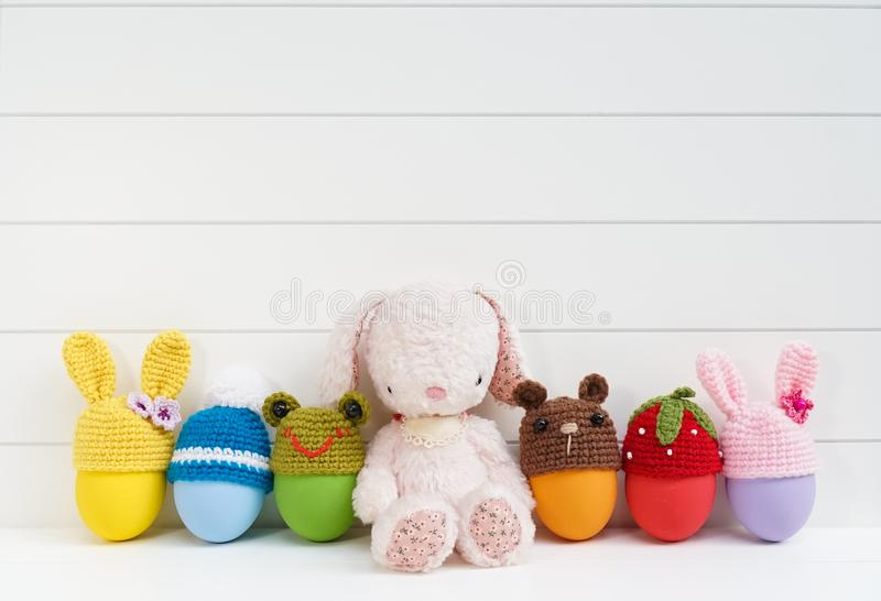 Cute plush bunny doll with colorful Easter eggs with crochet Easter egg cups top in various shapes of bunnies, frog, teddy stock photography