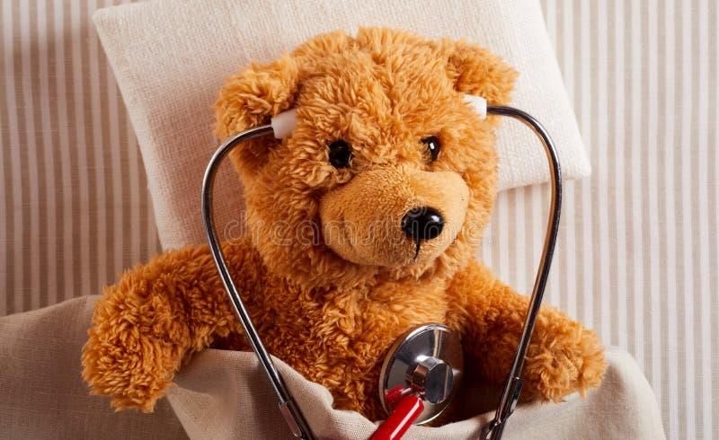Cute plush teddy bear using a stethoscope royalty free stock photography