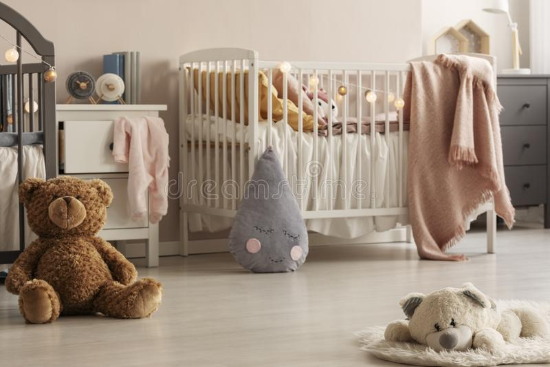 Cute plush toys and pink blankets in cozy bedroom interior for twin girls with two cribs and bedside cabinets. Real photo royalty free stock photography