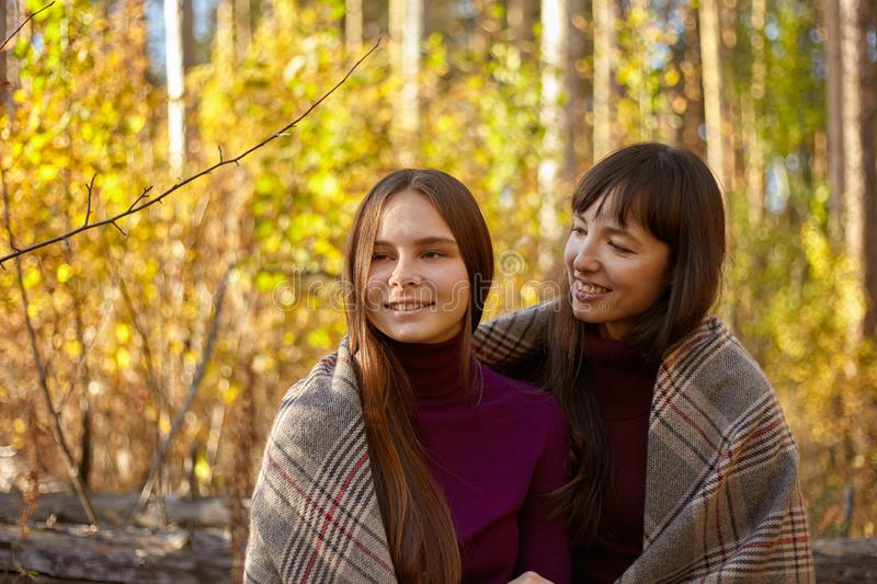Cute portrait of mother and daughter in the autumn forest. stock photography