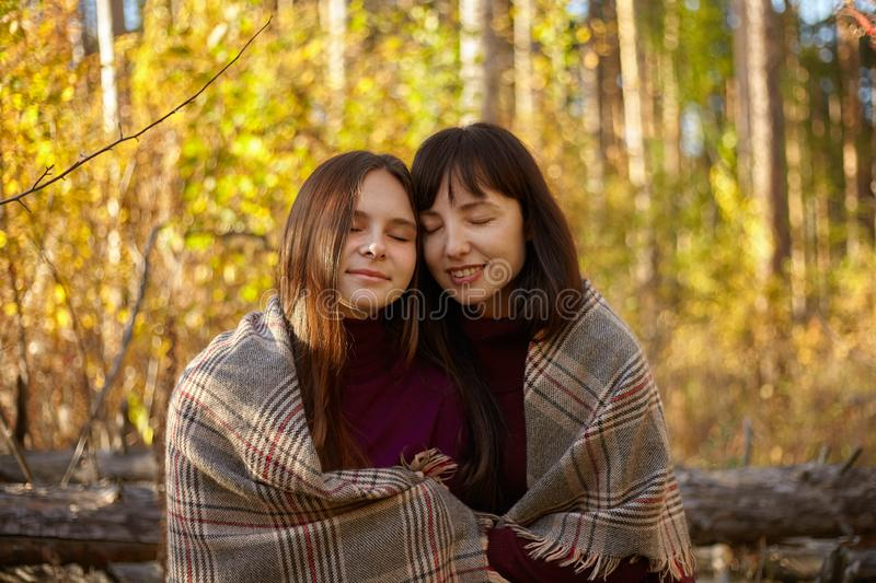 Cute portrait of mother and daughter in the autumn forest. royalty free stock images