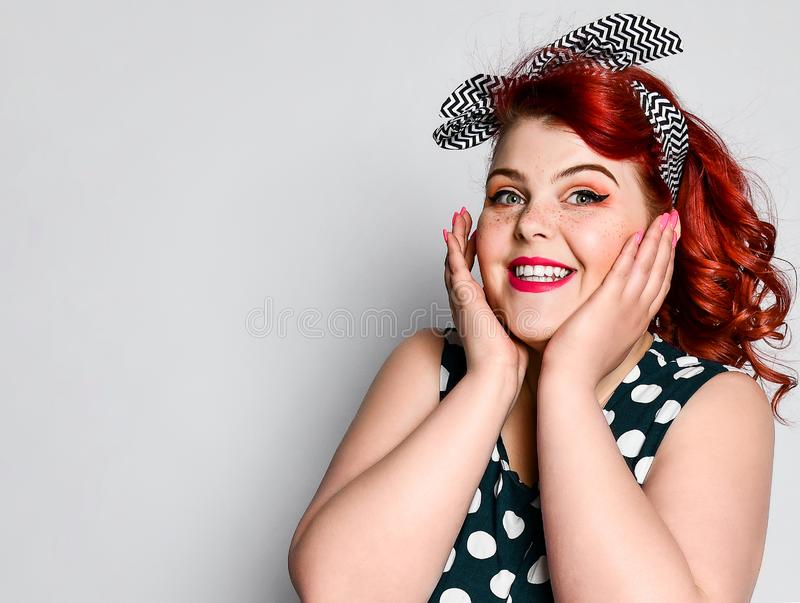 Pin up woman portrait. Beautiful retro female in polka dot dress with red lips and manicure nails and old fashion hairstyle. Cute portrait of a red-haired fat royalty free stock photography