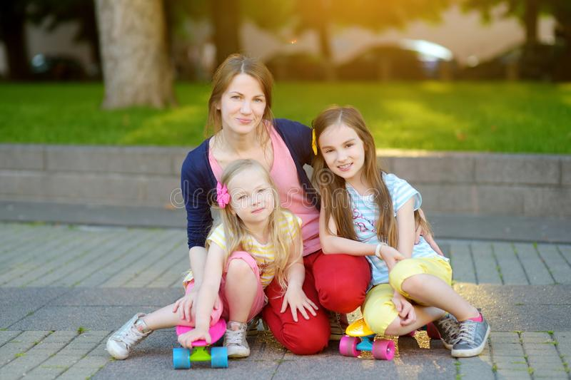 Cute portrait of young mother and two children riding skateboards in a city park on sunny summer evening royalty free stock photo