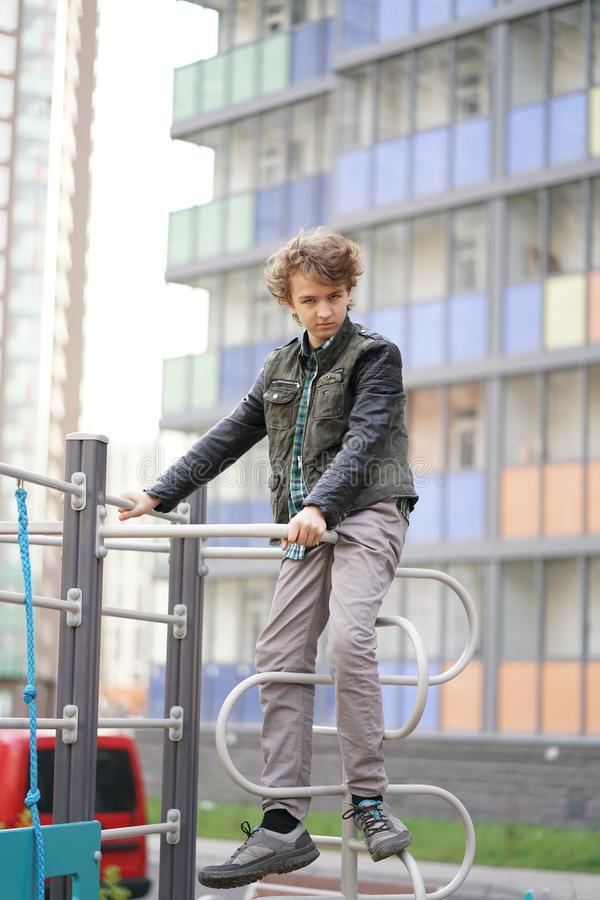 Cute positive boy teenager on the Playground in the city alone stock images